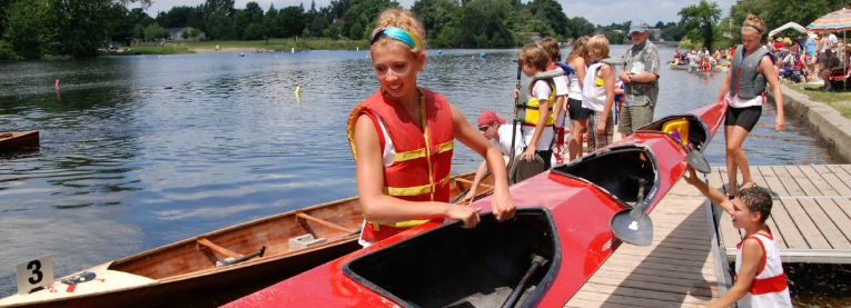 Girl lifting kayak out of the river at the Canoe Club in Carleton Place